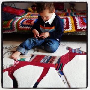 Le petit Lucca assit sur le tapis Biche
